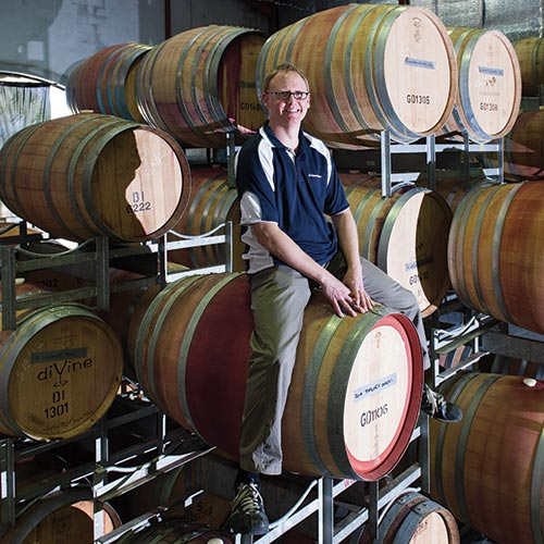 Marcus Bridges, cellar door manager at De Bortoli Wines, sitting on a barrel
