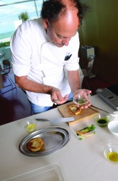 Moreno Cedroni plating the celerianc and lime puree with arugula sauce