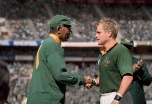 Nelson Mandela (actor Morgan Freeman) shakes hands with François Pienaar (actor Matt Damon).